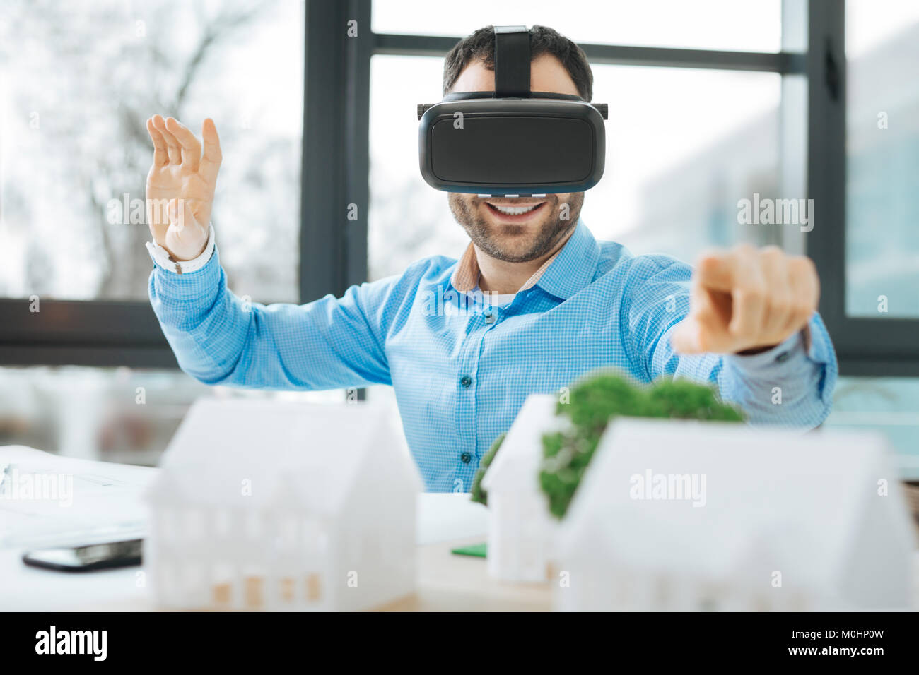 Cheerful architect in VR headset looking at models and smiling - Stock Image