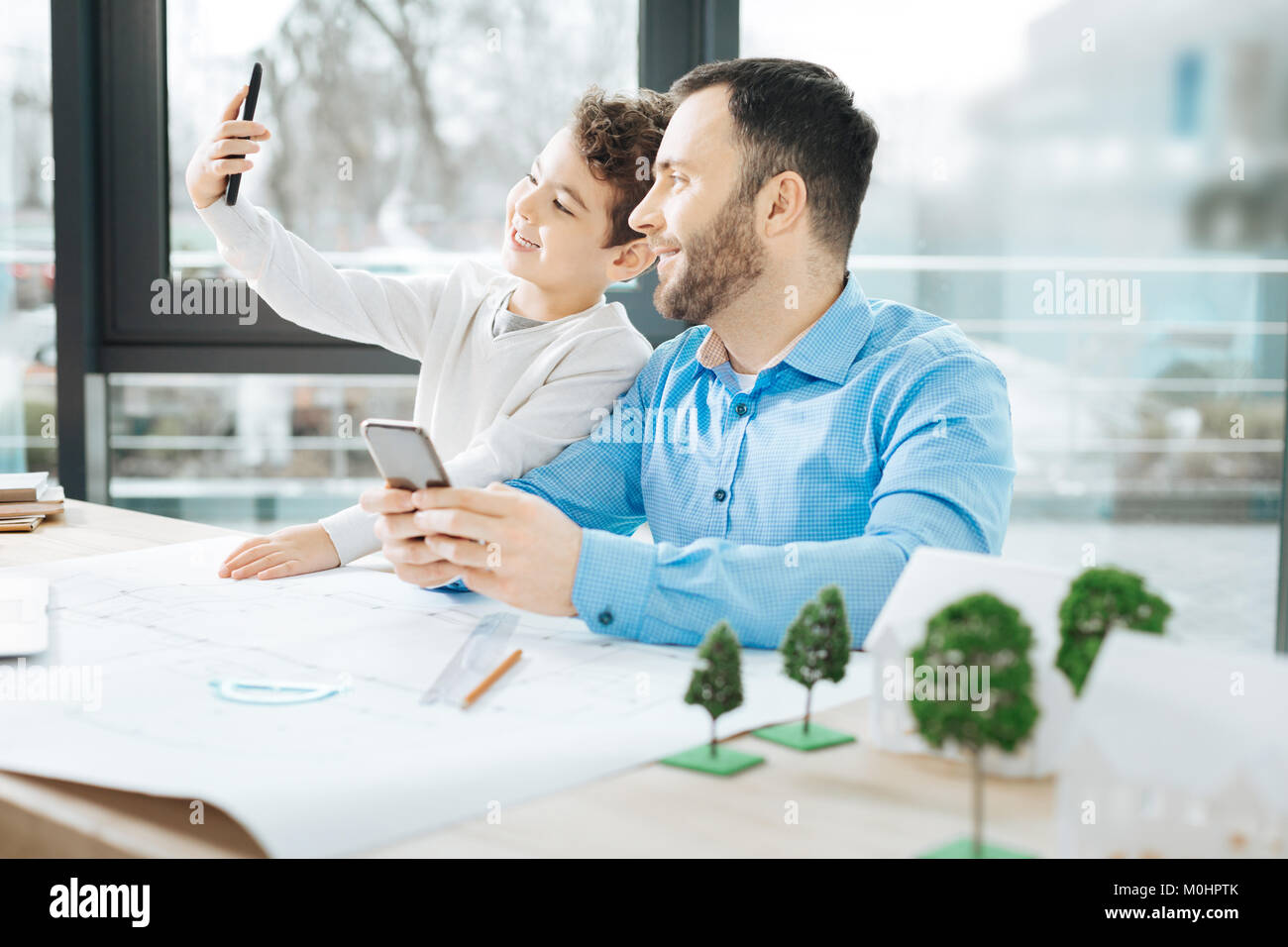 Cheerful boy taking a selfie with his father at work - Stock Image