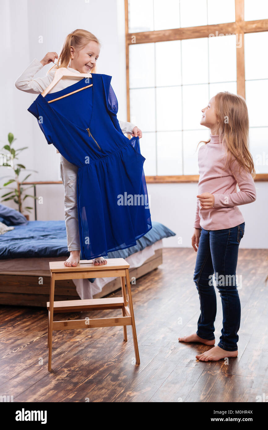 Funny young sisters trying on their moms dress - Stock Image