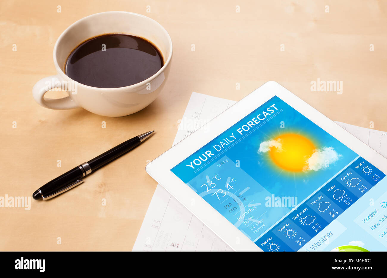 Workplace with tablet pc showing weather forecast and a cup