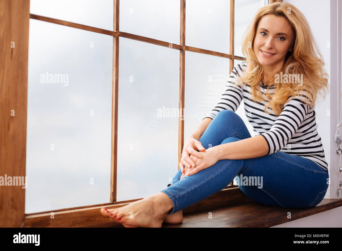 Happy young woman sitting on a windowsill Stock Photo