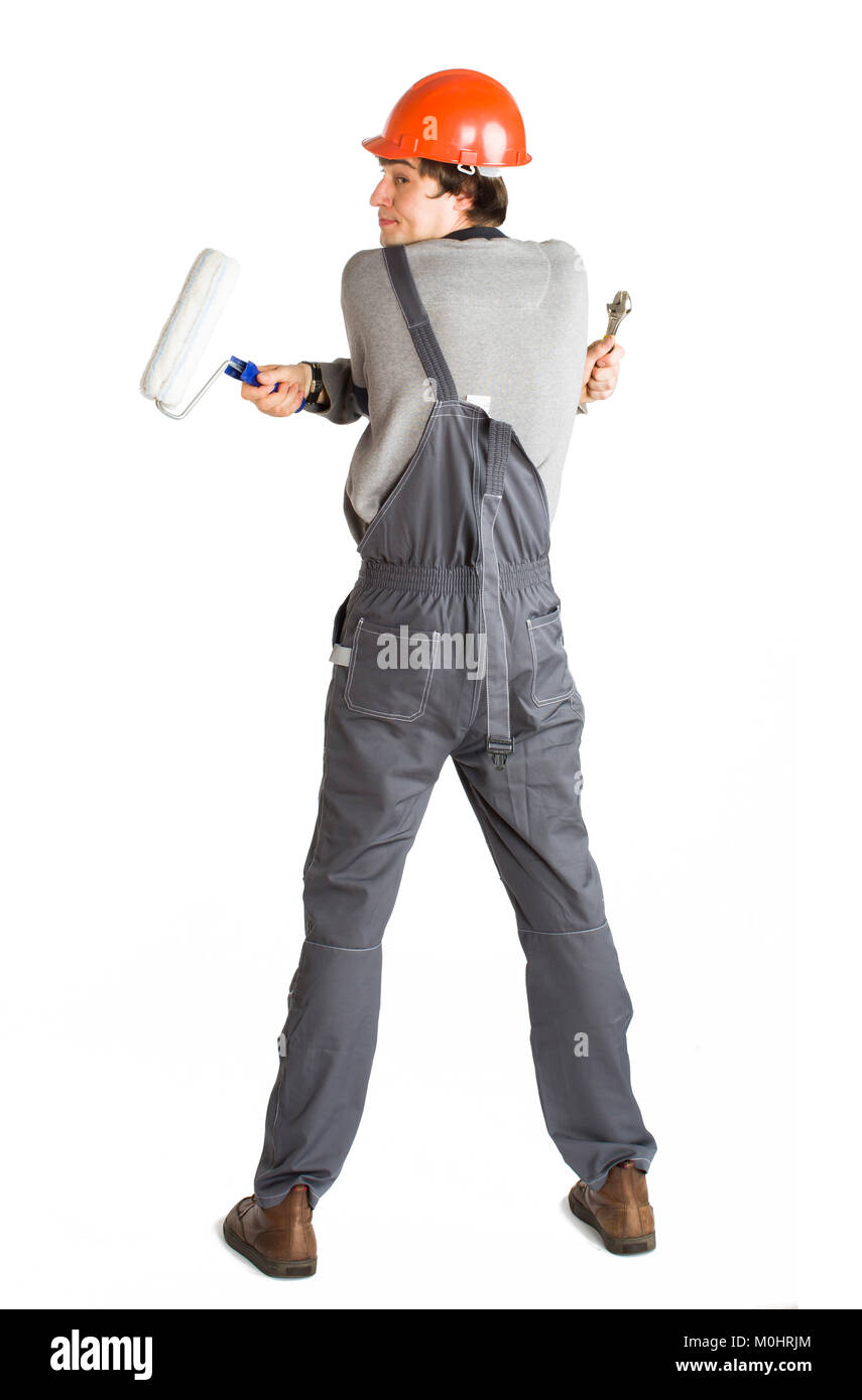 A young man in working grey clothes and orange hard helmet painting the walls in the room. - Stock Image