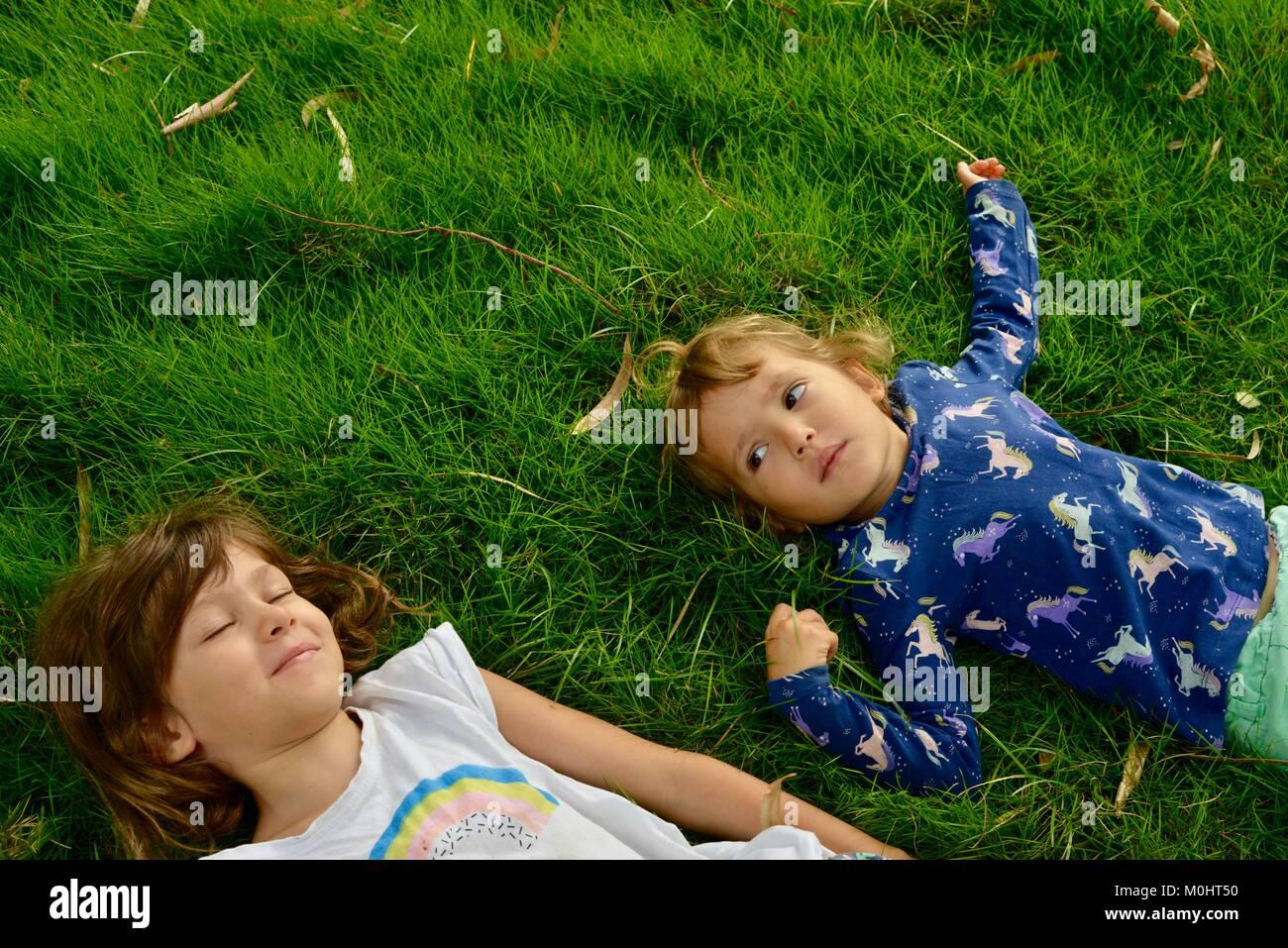 Two young girls lie on grass, portrait, Anderson Park Botanic Gardens, Townsville, Queensland, Australia Stock Photo