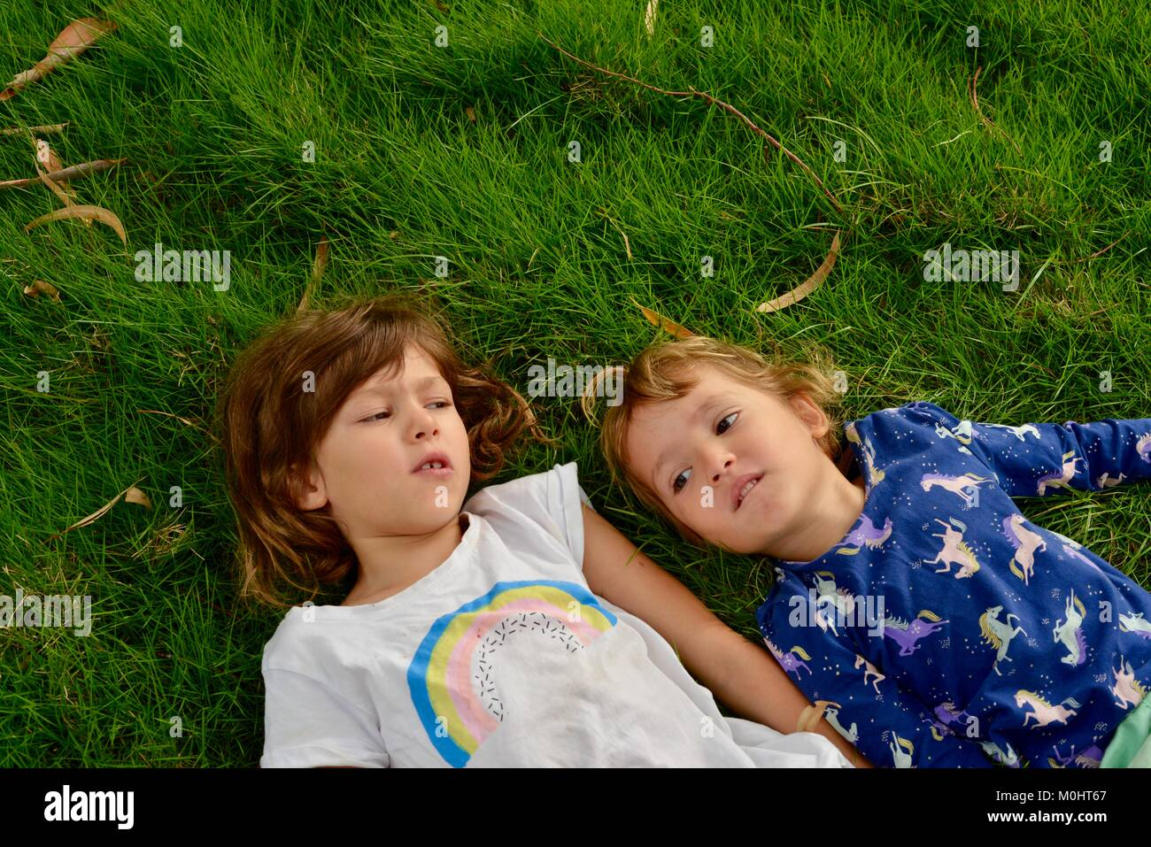 Two young girls lie on grass, portrait, Anderson Park Botanic Gardens, Townsville, Queensland, Australia Stock Photo