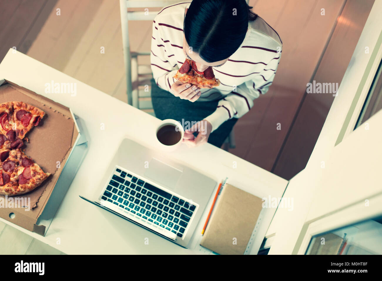 Top view of dark-haired woman eating pizza at workplace - Stock Image
