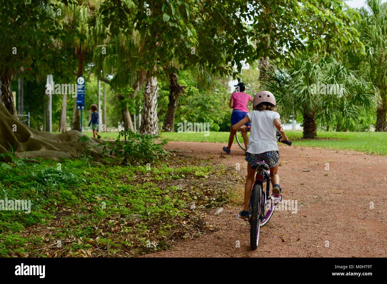 Young girl rides bike on a path with mother and sister walking, Anderson Park Botanic Gardens, Townsville, Queensland, Stock Photo