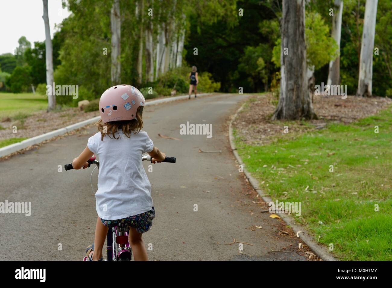 Young girl rides a bike on the road through Anderson Park Botanic Gardens, Townsville, Queensland, Australia Stock Photo