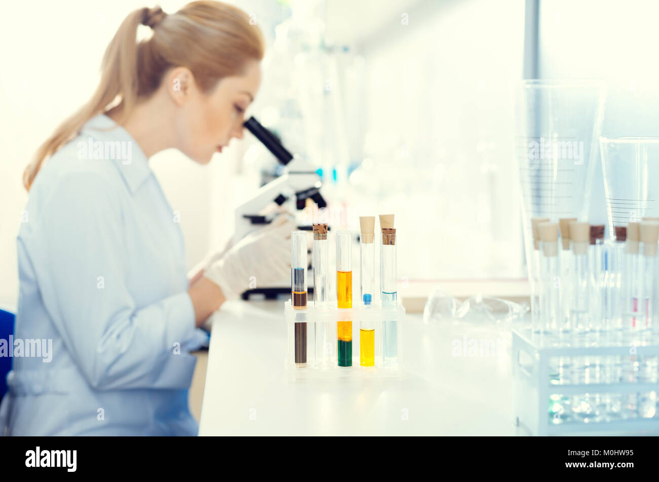 Female lab worker analyzing sample under microscope - Stock Image
