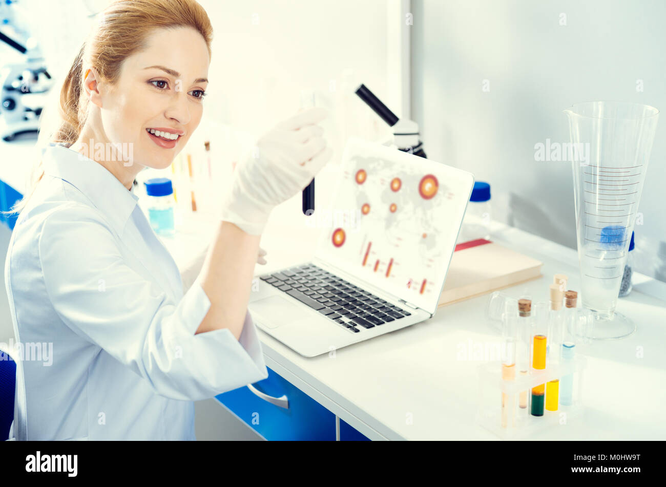 Adult woman analyzing test tube while working in lab - Stock Image