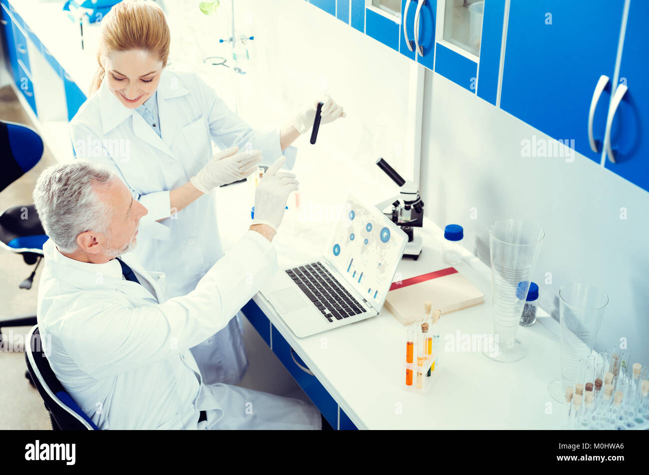 Smiling statists consulting during chemical experiment - Stock Image