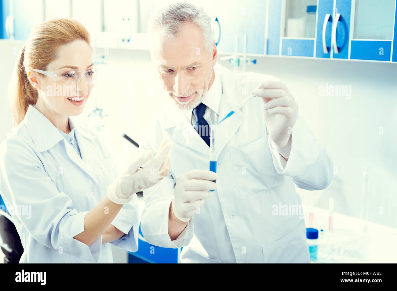 Mature scientist doing research together in lab - Stock Image