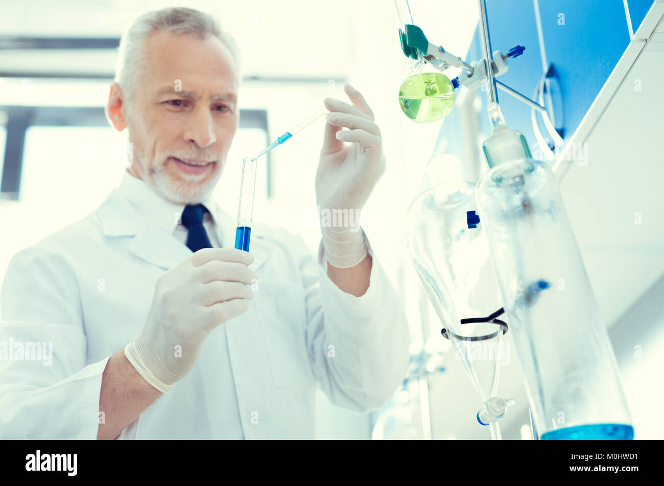 Positive minded scientist mixing chemical liquids in lab - Stock Image