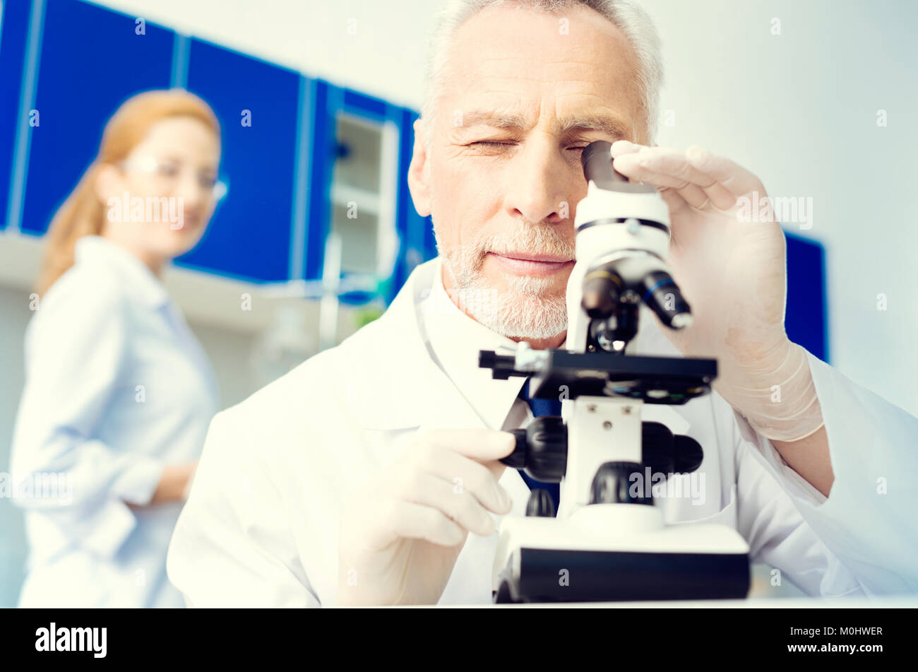 Positive minded researcher looking at sample under microscope - Stock Image