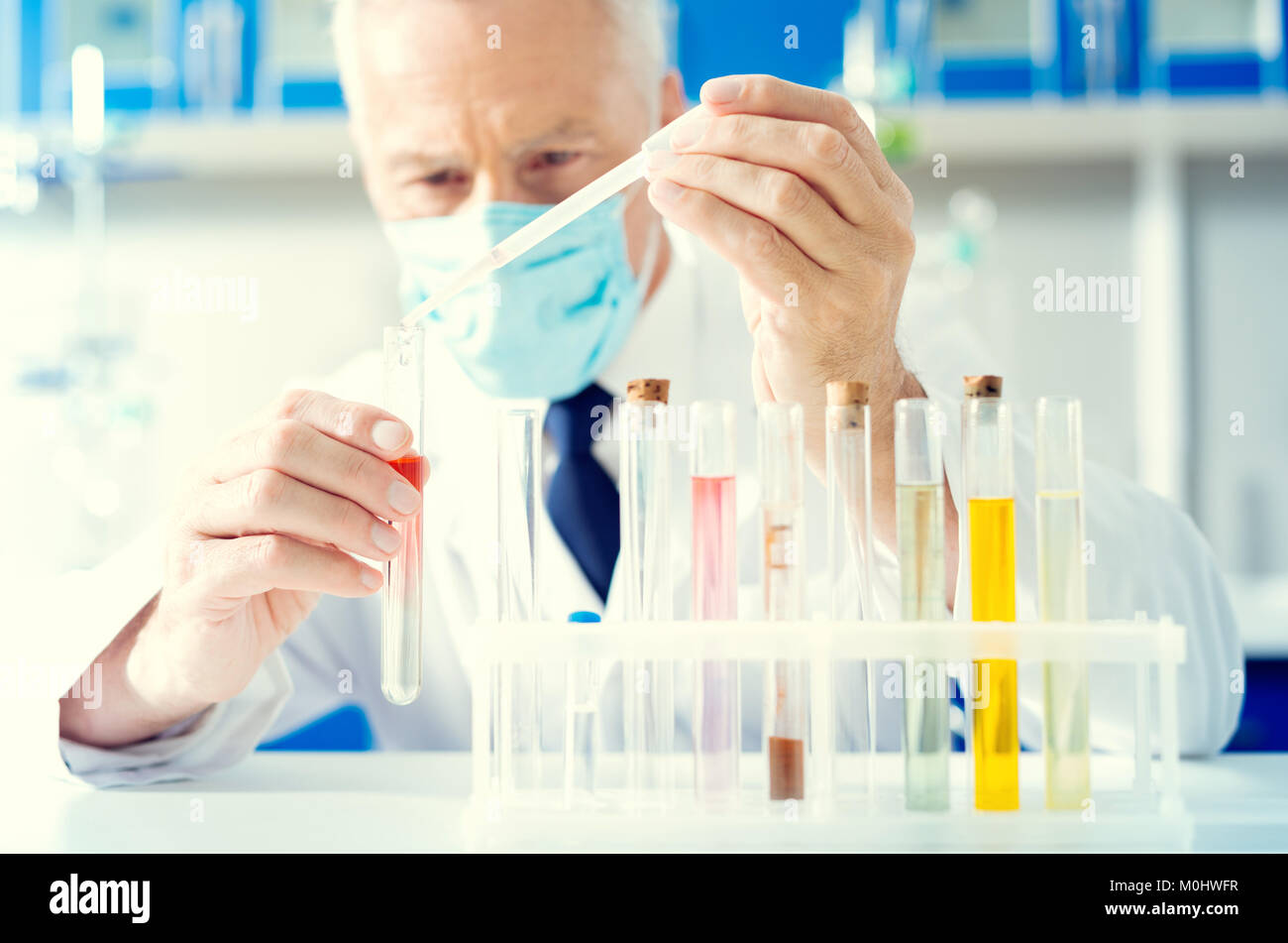 Close up of man pouring chemical liquid into test tube - Stock Image