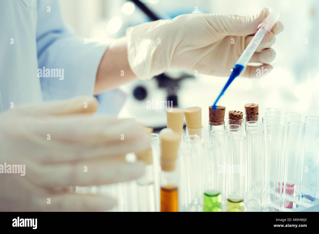 Lab worker using pipette while working with liquids - Stock Image