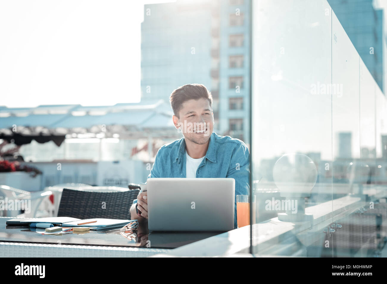 Pensive college guy dreaming while doing home assignment - Stock Image