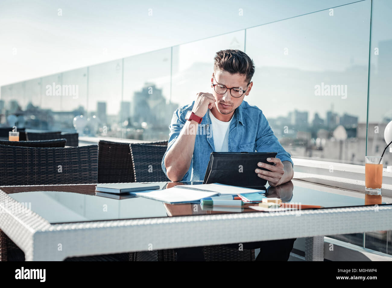 Focused young man working on touchpad in cafe - Stock Image