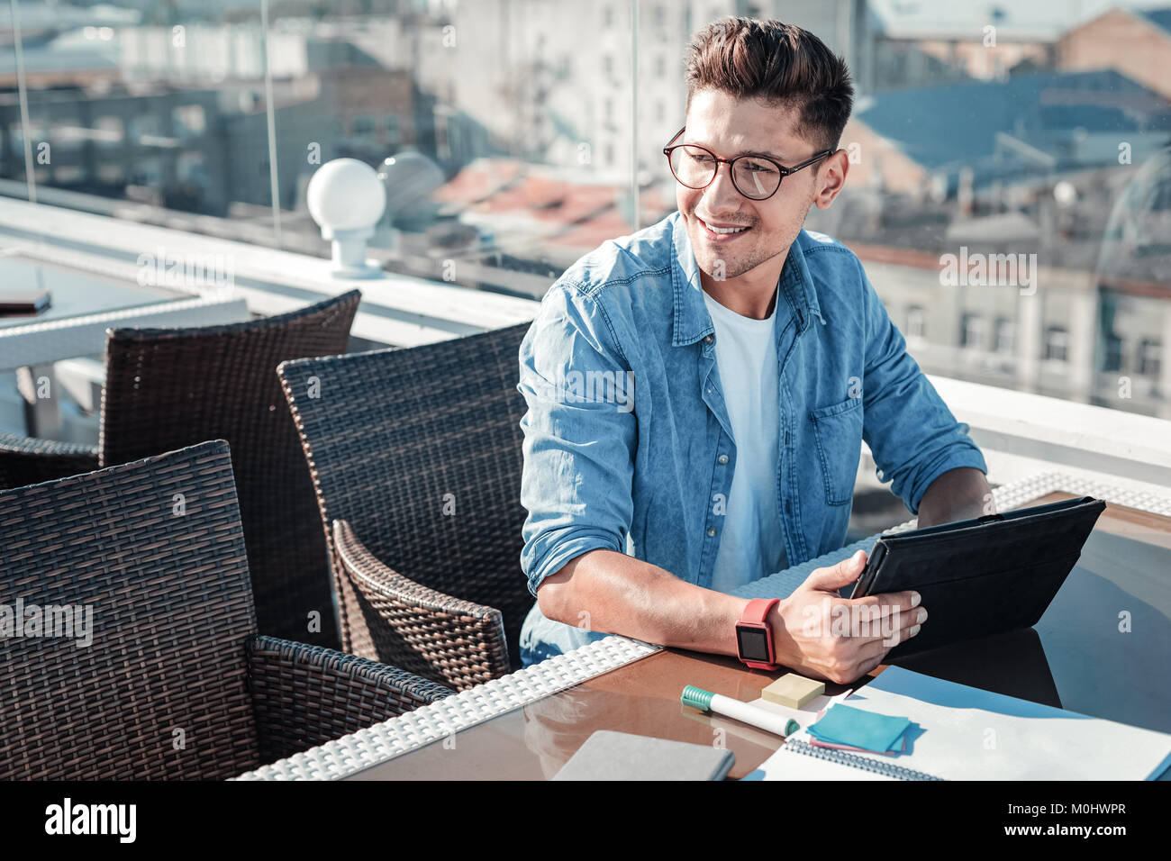 Dreamy young freelancer thinking of something and smiling - Stock Image