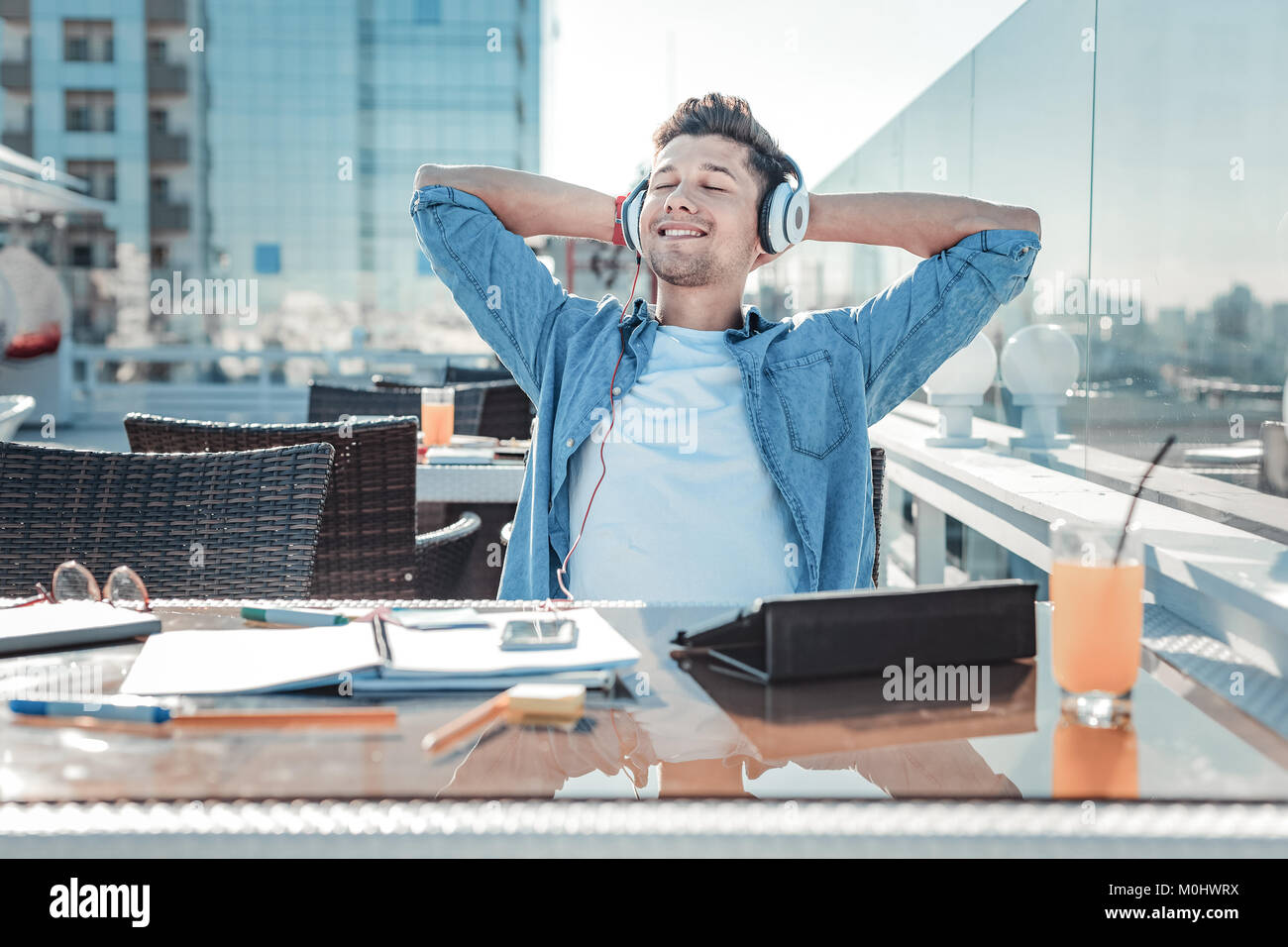 Dreamy guy taking break after studying outdoors - Stock Image
