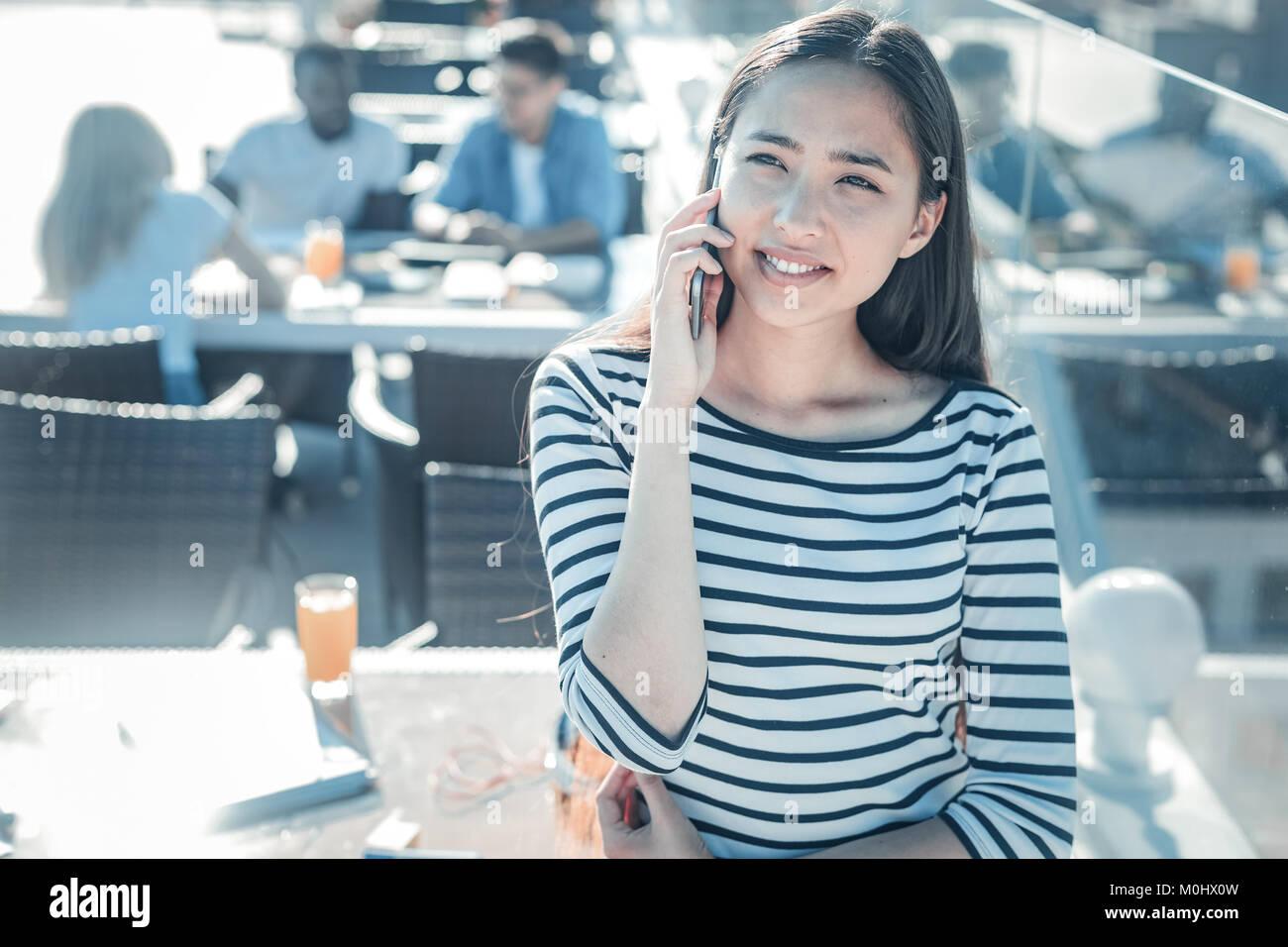 Smiling girl enjoying phone conversation - Stock Image