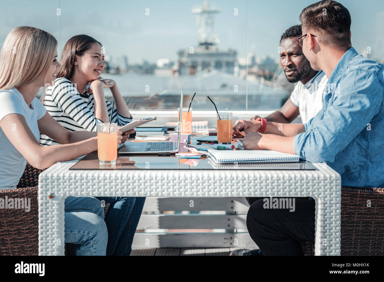 Group of young freelancers meeting in cafe for lunch - Stock Image
