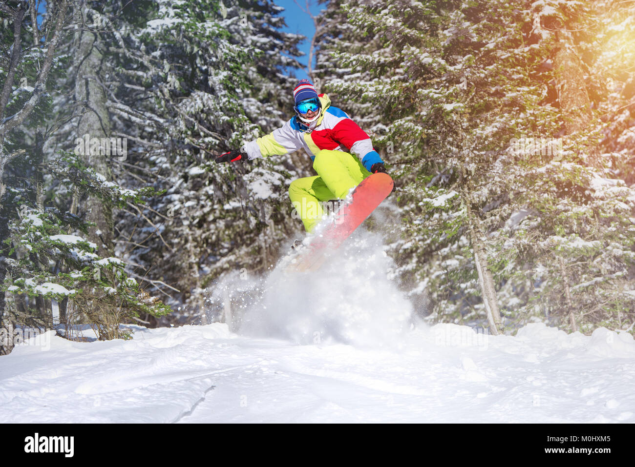 Snowboarder backcountry jump offpiste against frozen forest - Stock Image