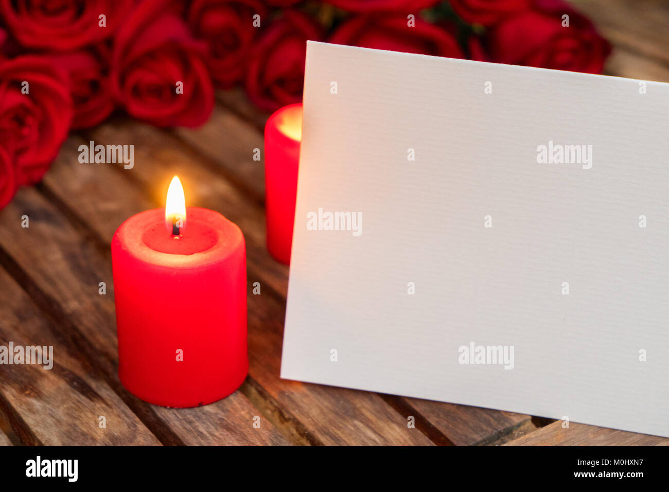 Two burning candles with fresh roses Stock Photo: 172497843