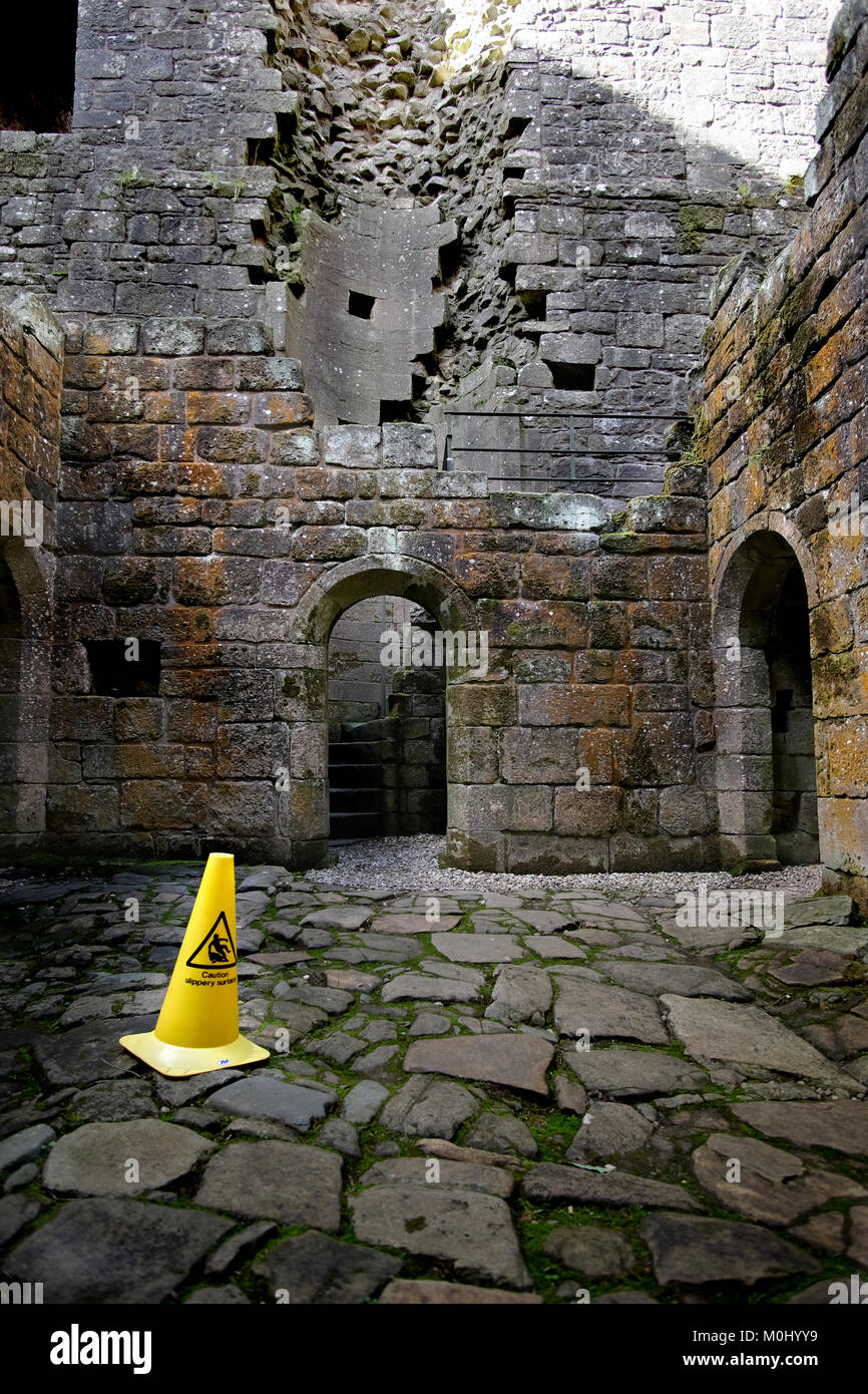 A caution slippery surface hazard bollard on the wet uneven floor at Hermitage castle - Stock Image