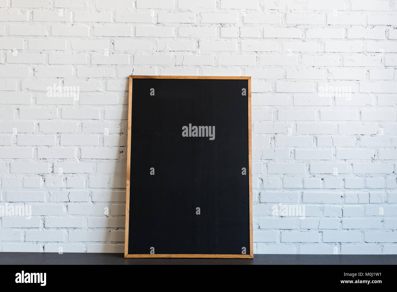 empty chalkboard in wooden frame standing at white brick wall Stock ...