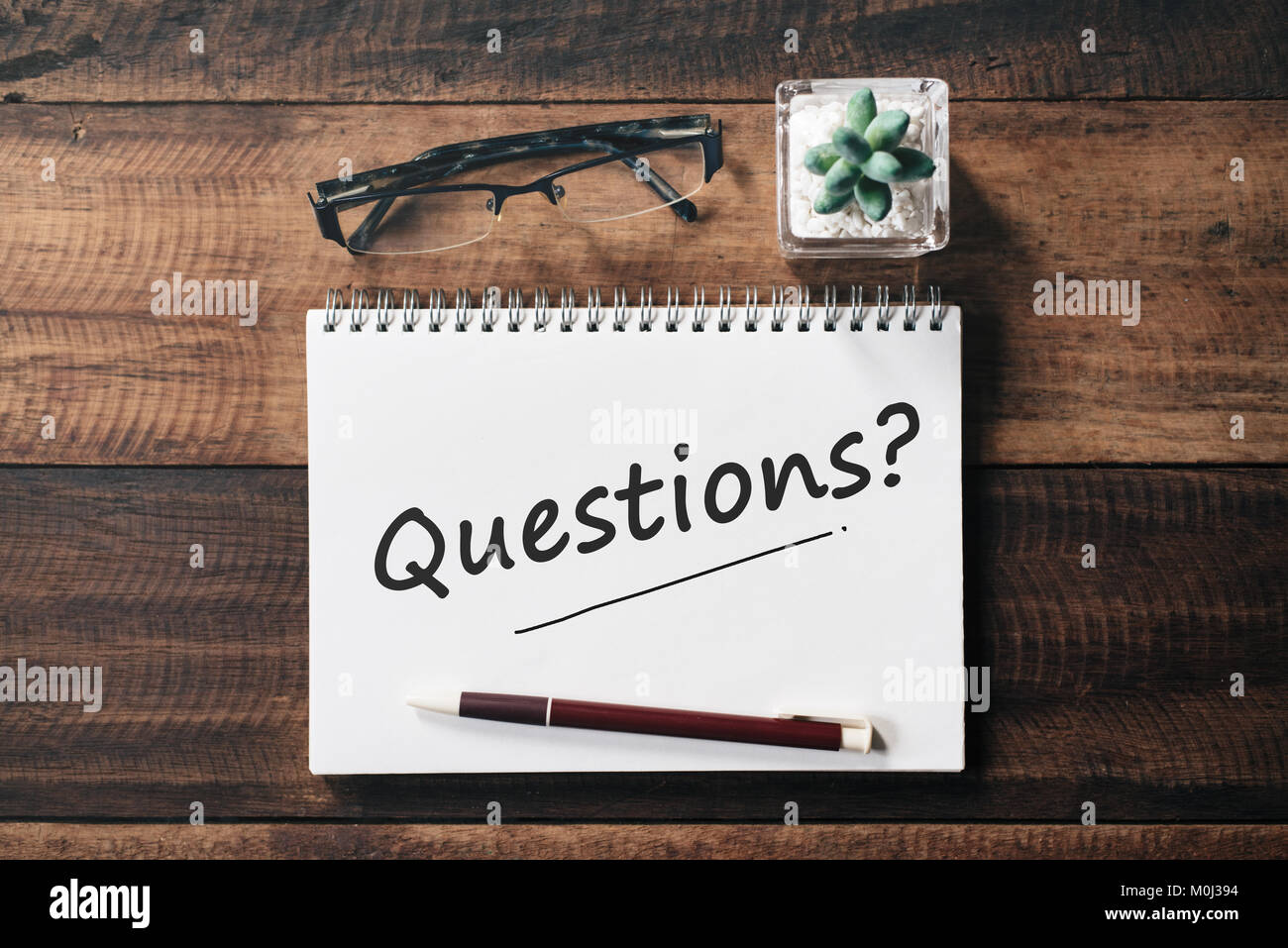 spectacle, cactus, pen and notebook with QUESTIONS word on wooden table. asking concept - Stock Image