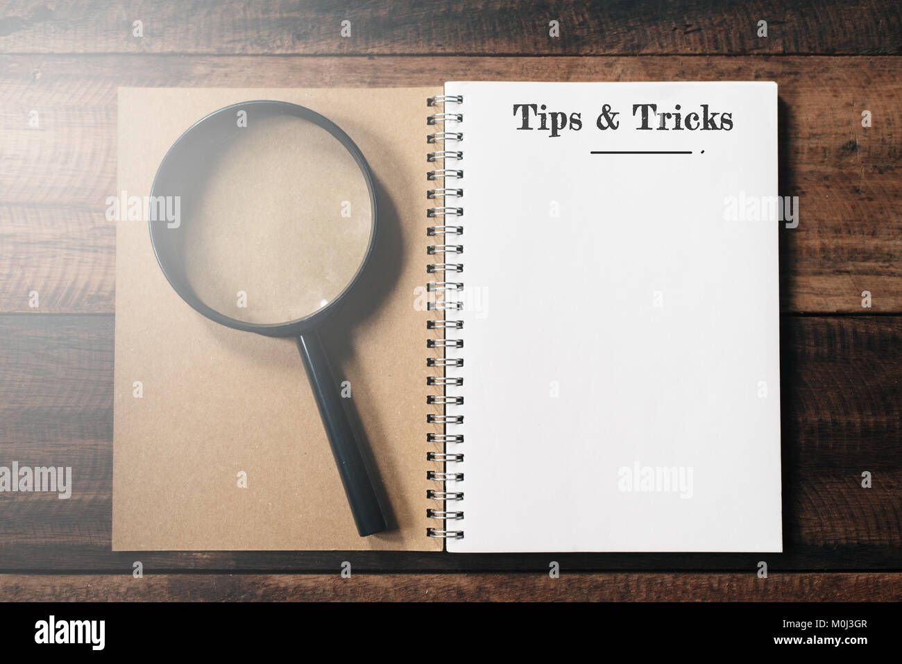 magnifying glass and notebook with TIPS AND TRICKS word with copy space on wooden table. tips and tricks concept - Stock Image