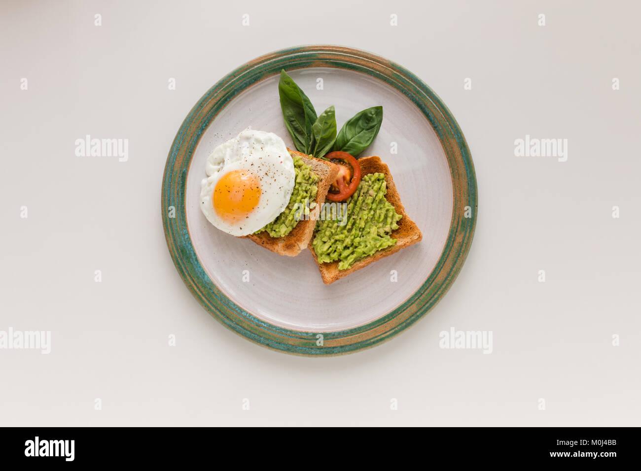 fried egg and avocado on toasts - Stock Image