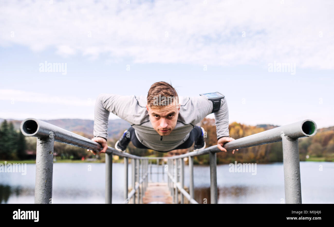 Young man with smartphone doing exercise in park. - Stock Image