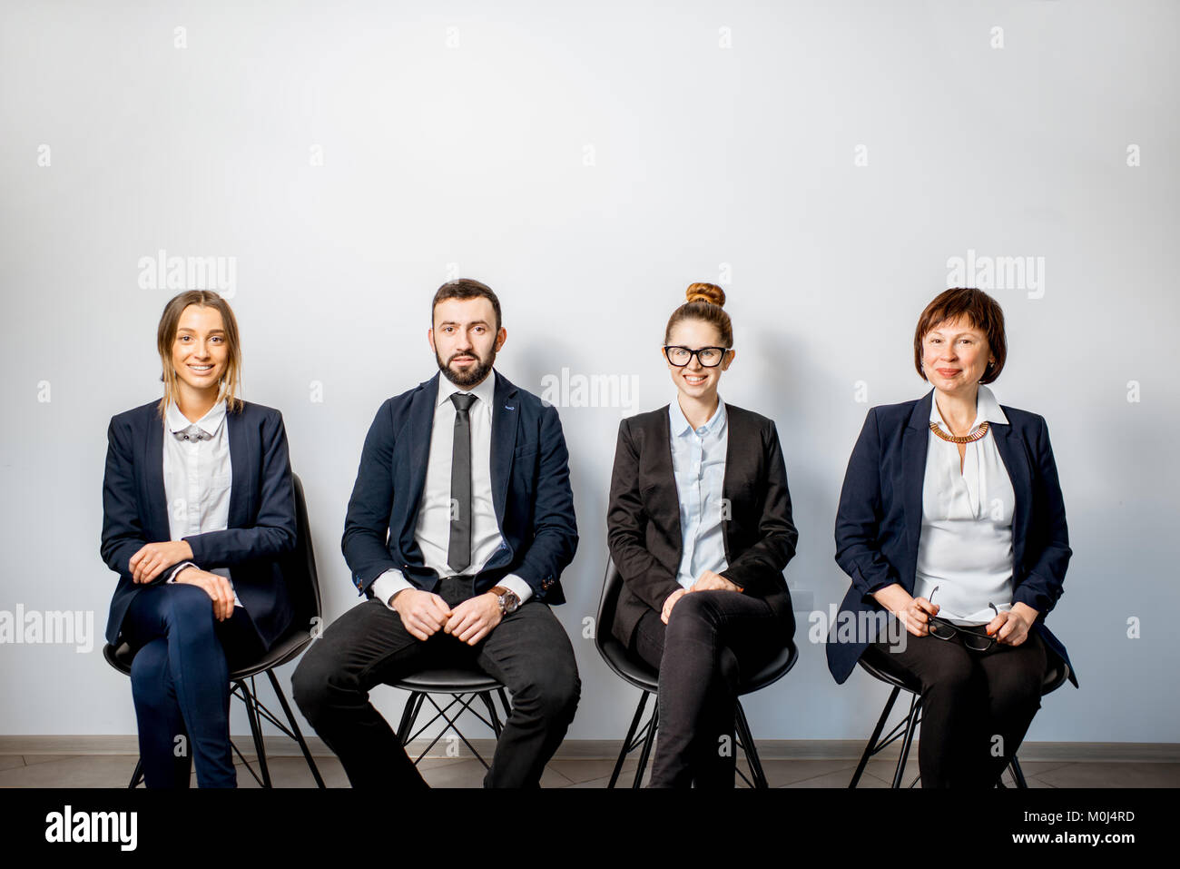 Business people sitting in a row - Stock Image