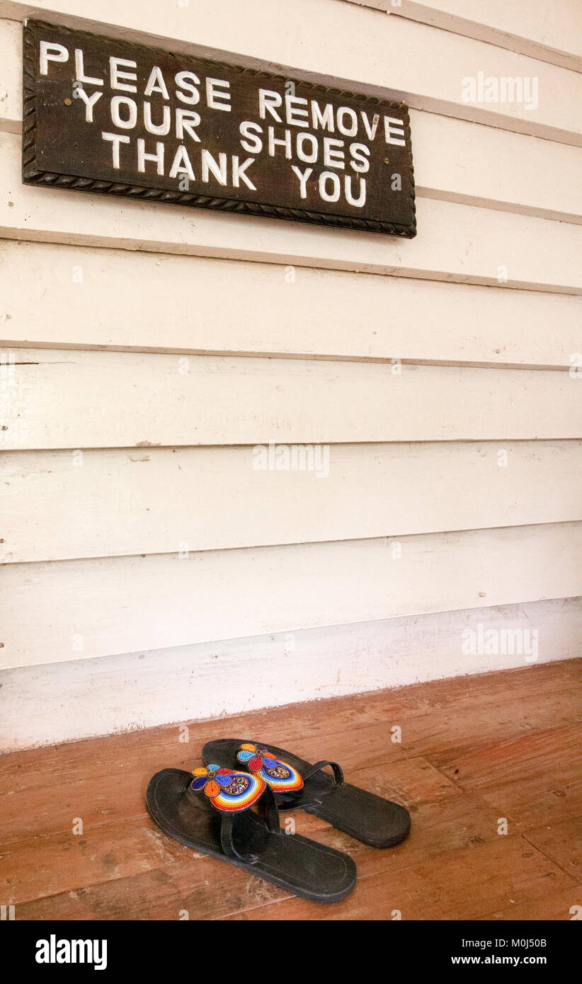 Sign on front porch requesting shoes to be removed Stock Photo