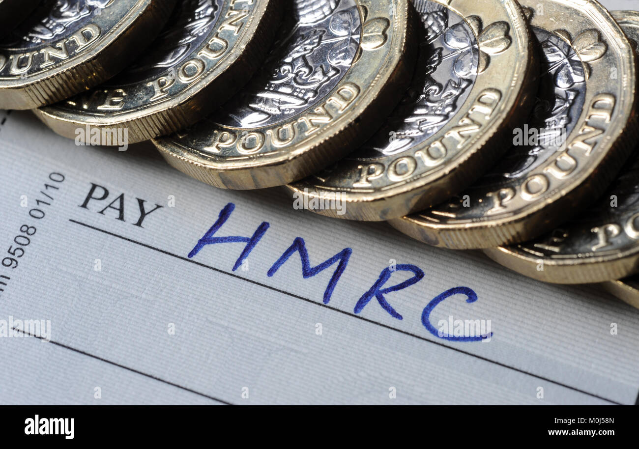 CHEQUE BOOK AND ONE POUND COINS WITH HMRC PAY NAME RE TAX INLAND REVENUE TAXATION AVOIDANCE EVASION ETC UK - Stock Image