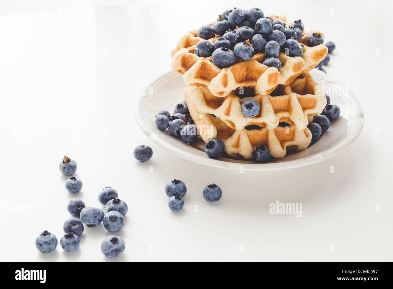 plate of tasty fresh stacked belgian waffles with blueberries - Stock Image
