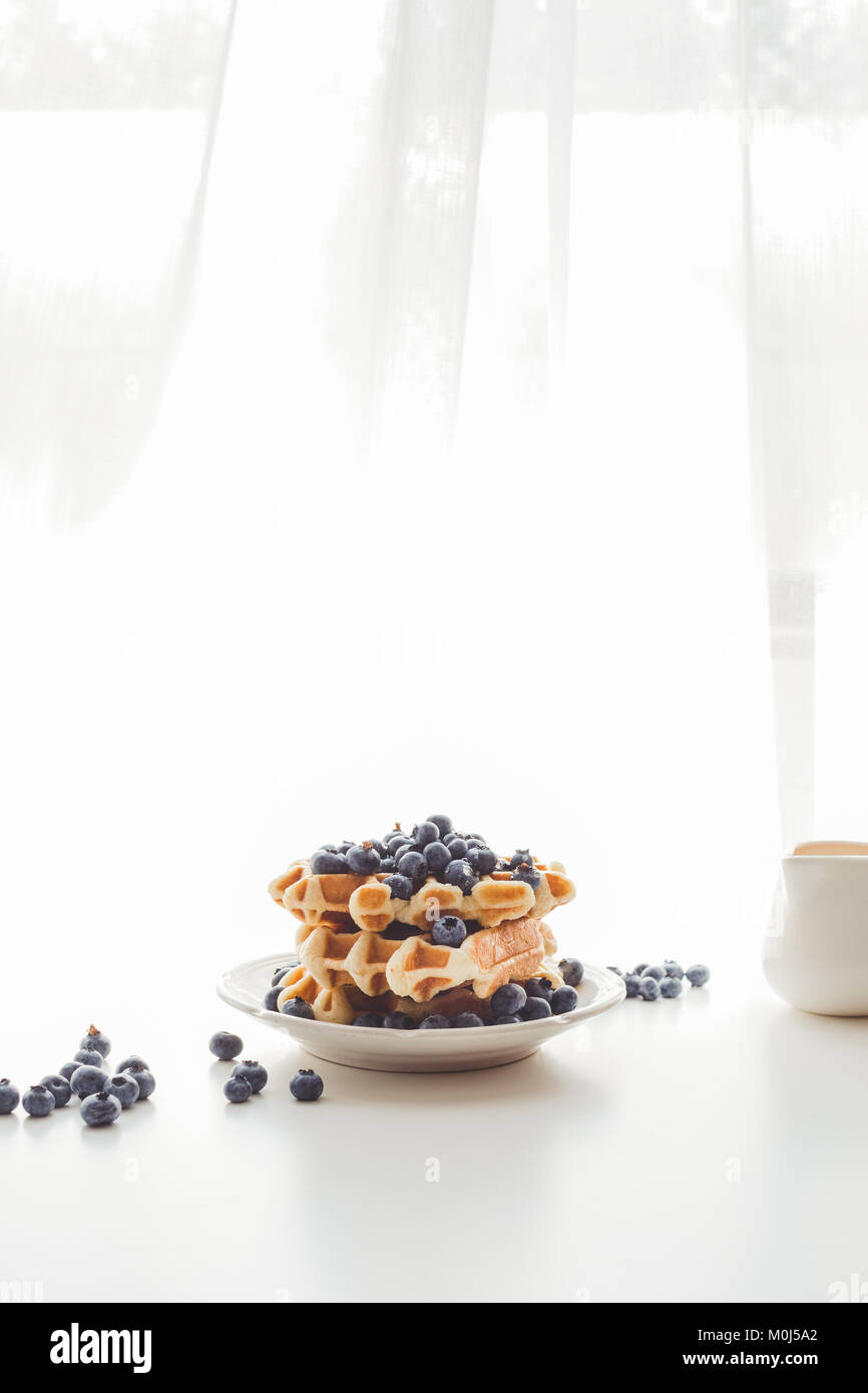 plate of freshly baked waffles with blueberries - Stock Image