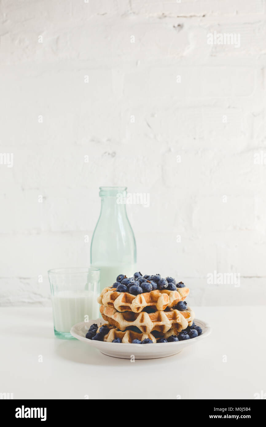 delicious breakfast of waffles with blueberries and glass of milk - Stock Image