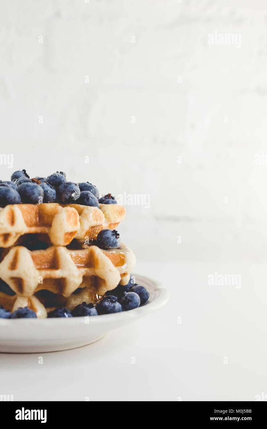 plate of fresh waffles stack with blueberries - Stock Image