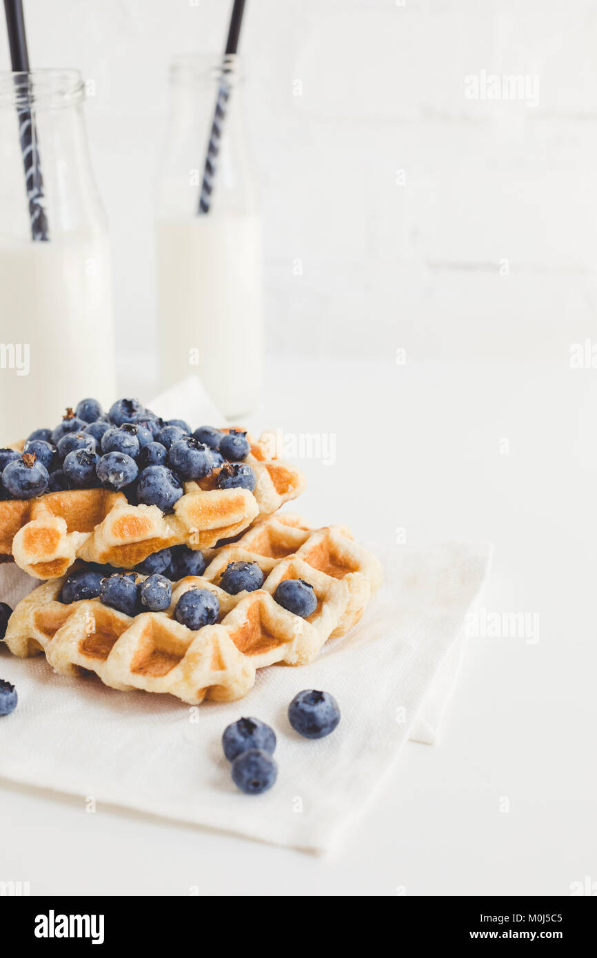 delicious breakfast of freshly baked waffles with blueberries and milk - Stock Image