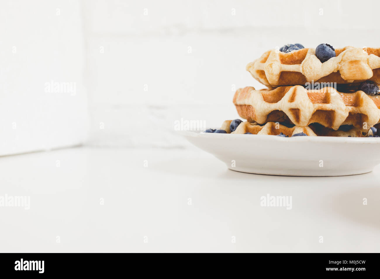 plate of delicious fresh waffles with blueberries - Stock Image