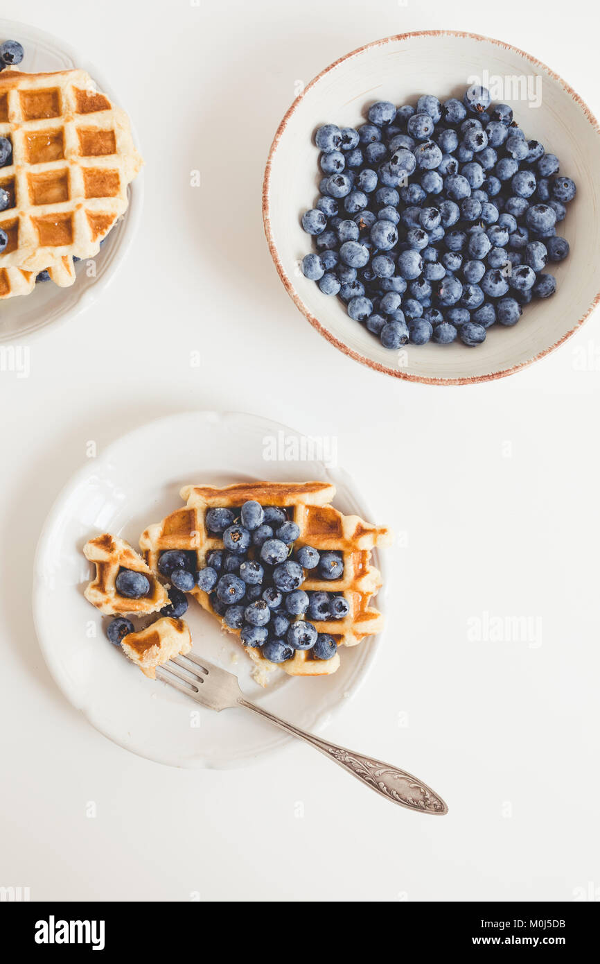 composition of waffles and blueberries in plates for breakfast - Stock Image