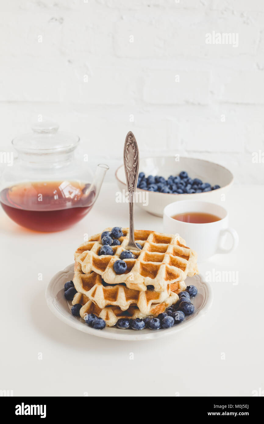 tasty breakfast of waffles with blueberries and tea - Stock Image