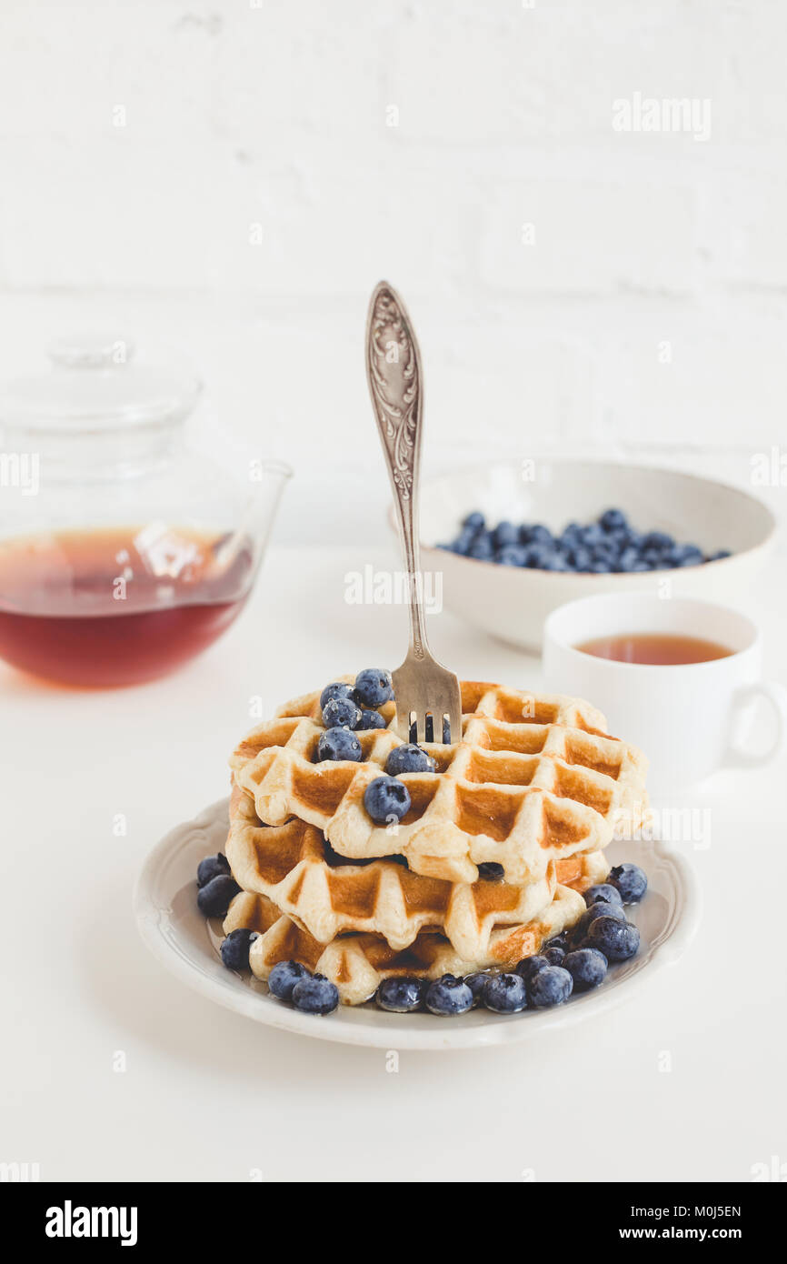 delicious breakfast of tasty waffles with blueberries and tea - Stock Image