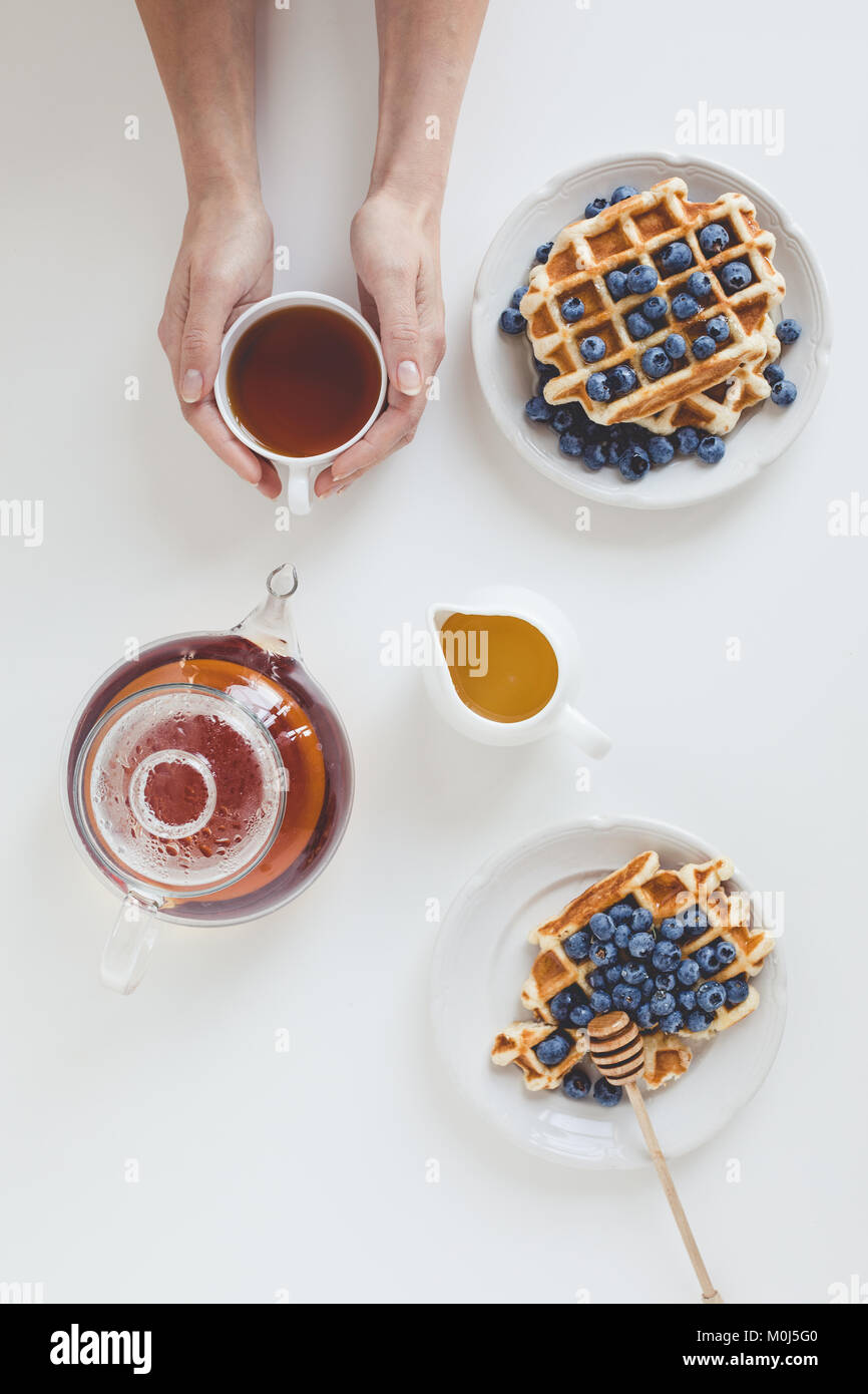 top view of delicious breakfast of waffles and tea in female hands - Stock Image