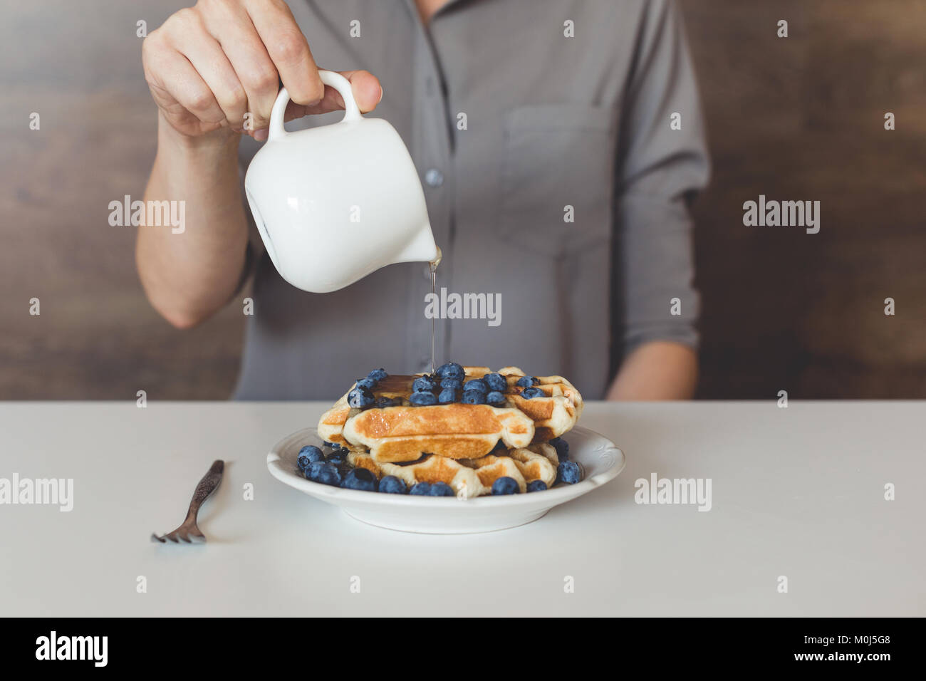 cropped shot of woman pouring sweet syrup on tasty waffles - Stock Image