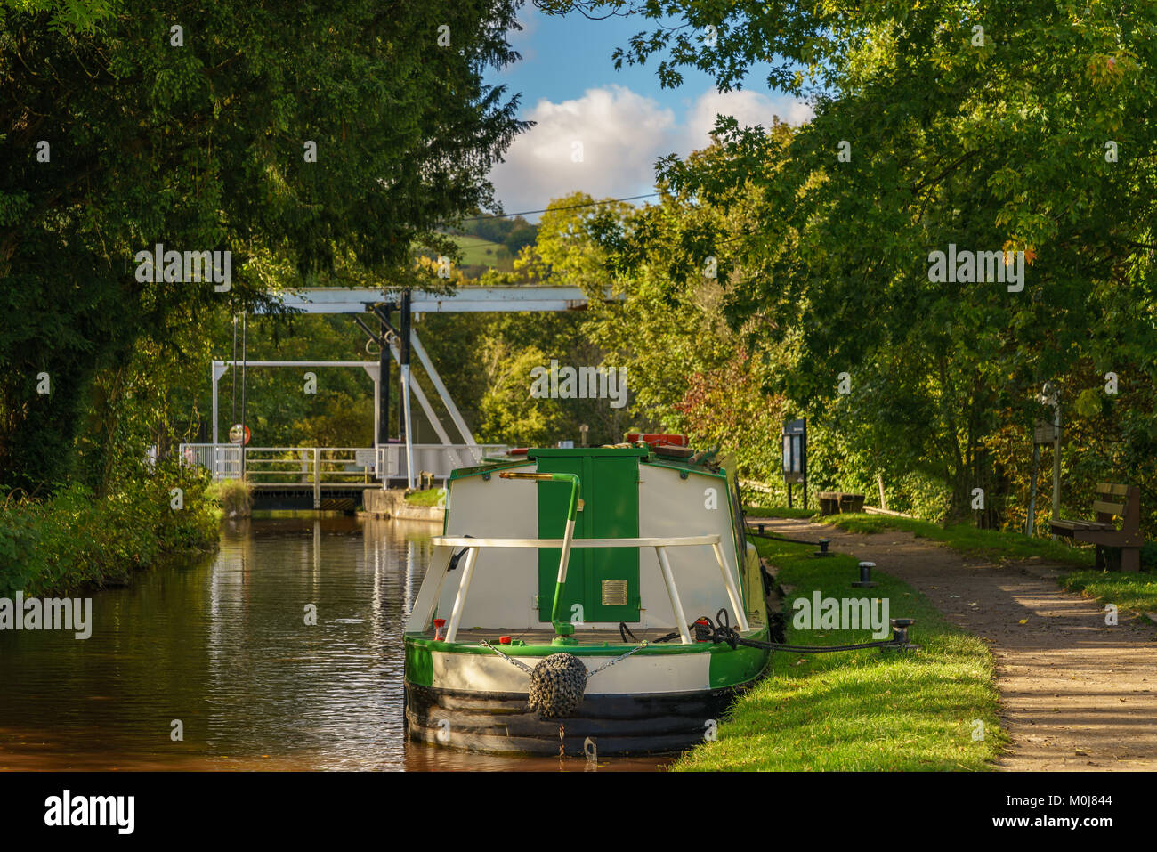 The Monmouthshire & Brecon Canal with a boat and the lift bridge, seen in Talybont on Usk, Powys, Wales, UK - Stock Image