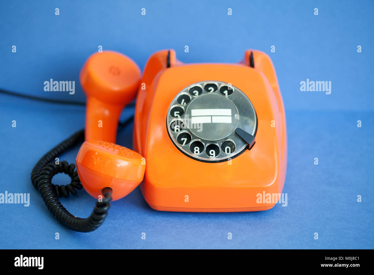 Busy retro phone orange color, handset receiver on blue background. Shallow depth field photography. Stock Photo