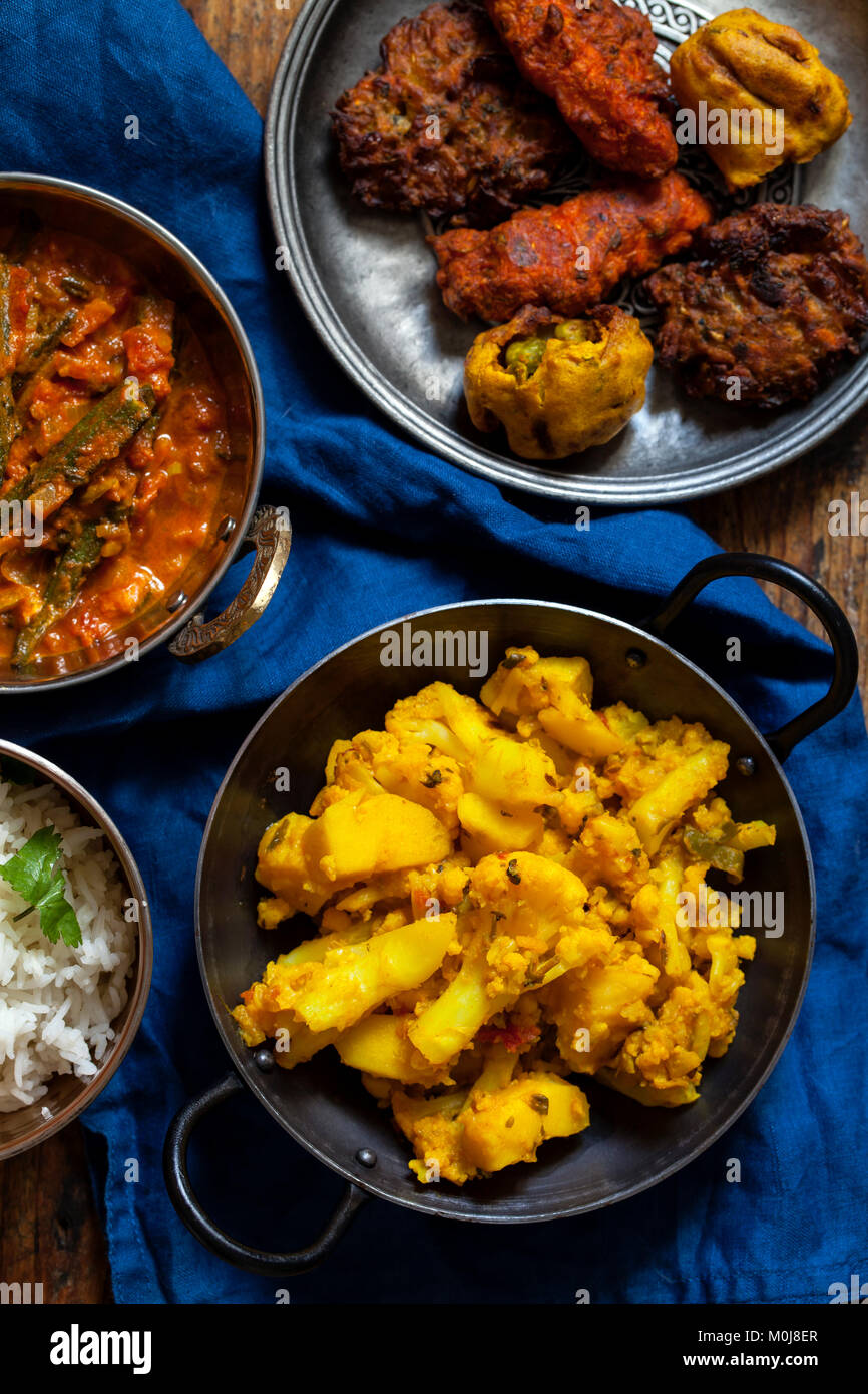 Indian meal with aloo gobi, okra curry, rice and pakoras - Stock Image